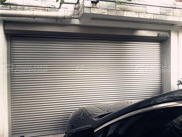 格拉夫卷帘具有以下特点: 遮阳 铝合金制成的帘片具有100%的遮光率,因此节能卷帘系统在完全放下时能阻挡绝大部分的阳光,有效隔绝夏日阳光的热量。在烈日炎炎的夏日,格拉夫多功能卷帘的遮阳效果即可帮助降低房屋空调能耗20%以上。帘片的挂钩部分有规则的开孔,可以自由调节室内采光和通风,保证室内环境处于理想状态。 防盗 多功能卷帘的帘片是连成一个整体的,具有相当的强度,升降装置具有自锁功能,并且在卷帘系统的上端还安装有防上推装置,可以阻止外力的撬动,防止窃贼采用撬棍入室行窃。具有专利技术的防风防盗导轨及双排侧扣系