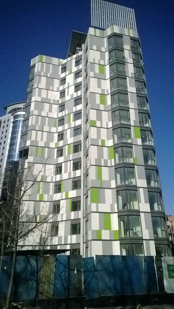 """精心设计,打造简约时尚的现代建筑风格 北京新派白领公寓由德国设计师团队精心设计打造,建筑外墙采用了埃特尼特佳美板。埃特尼特佳美板是一种通体一色的纤维水泥板,表面具有独特的植物纤维纹理,自然生动,与众不同。该项目采用了白色和浅灰色的经典搭配,形成简约而时尚的现代建筑风格,加上象征着生命力的绿色点缀,彰显都市白领的青春活力,生动地表现了""""艺术与休闲交呼应,居住与生活相融合""""的设计理念。 理念创新,打造都市白领全新的居住方式 新派公寓(CYPA,China Young Professi"""
